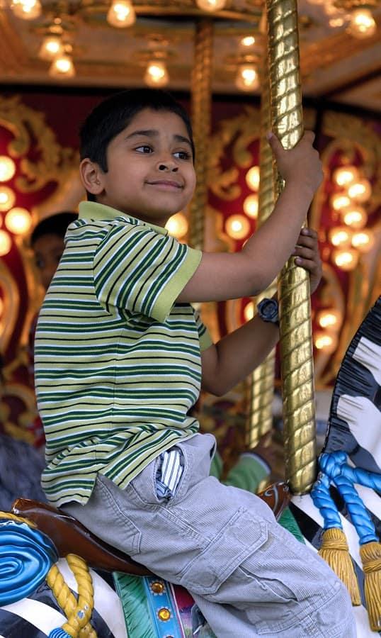 boy sitting on merry go round